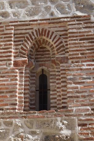 Detalle de un vano de la torre con doble arco de herradura apuntado de ladrillo enmarcado por alfiz.